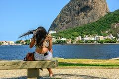 Den härliga kvinnan med att flyga sammanträde för svart hår på bänken på bakgrunden av Sugarloaf och Guanabara skäller i Rio de J royaltyfri bild