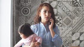 Den härliga kvinnan med behandla som ett barn i handen som har en pratstund vid telefonen arkivfilmer