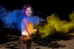 Den härliga kvinnan med blått och guling Holi pudrar exploderande aroun royaltyfri foto