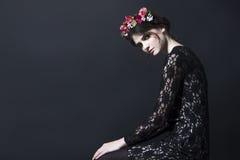 Den härliga kvinnan med blommakanten på huvudet snör åt in klänningen Arkivfoton