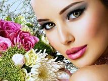 Den härliga kvinnan med buketten av ny spting blommar på framsidan Royaltyfri Bild