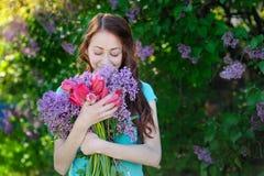 Den härliga kvinnan med en bukett av blommor som på våren går, parkerar Royaltyfria Foton