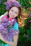 Den härliga kvinnan med en bukett av blommor som på våren går, parkerar Fotografering för Bildbyråer