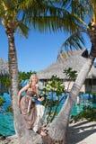 Den härliga kvinnan med en rose på en palmträd. Fotografering för Bildbyråer
