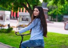 Den härliga kvinnan med en tappningcykel i en stad parkerar Fotografering för Bildbyråer