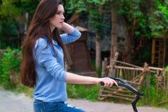 Den härliga kvinnan med en tappningcykel i en stad parkerar Royaltyfria Foton