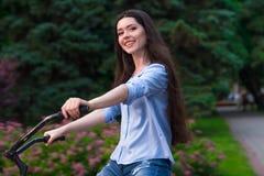 Den härliga kvinnan med en tappningcykel i en stad parkerar Royaltyfria Bilder