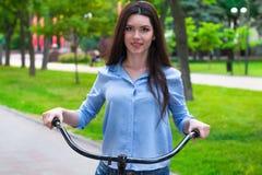Den härliga kvinnan med en tappningcykel i en stad parkerar Arkivfoton