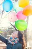 Den härliga kvinnan med färgrika ballonger parkerar på våren Royaltyfria Bilder