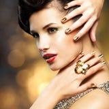 Den härliga kvinnan med guld spikar och cirkeln Arkivfoton