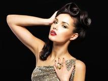 Den härliga kvinnan med guld- spikar och danar makeup Royaltyfri Bild