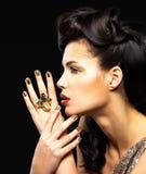 Den härliga kvinnan med guld- spikar och modemakeup Arkivfoto