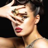 Den härliga kvinnan med guld- spikar och stilmakeup Royaltyfri Bild