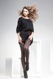 Den härliga kvinnan med långa sexiga ben klädde elegant posera i studion Royaltyfri Fotografi