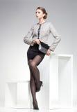 Den härliga kvinnan med långa sexiga ben klädde elegant posera i studion arkivbilder