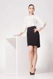 Den härliga kvinnan med långa sexiga ben klädde elegant posera i studion Royaltyfri Foto
