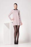 Den härliga kvinnan med långa sexiga ben klädde elegant posera i studion Fotografering för Bildbyråer