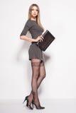 Den härliga kvinnan med långa sexiga ben klädde elegant posera i studion Arkivfoto