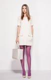 Den härliga kvinnan med långa sexiga ben klädde elegant posera i studion Arkivfoton