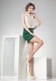 Den härliga kvinnan med långa sexiga ben klädde elegant posera i studion - full kropp Fotografering för Bildbyråer