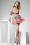 Den härliga kvinnan med långa sexiga ben klädde elegant posera i studion - full kropp Arkivbilder