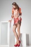 Den härliga kvinnan med långa sexiga ben klädde elegant posera i studion - full kropp Royaltyfri Bild