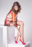 Den härliga kvinnan med långa sexiga ben klädde elegant posera i studion - full kropp Arkivbild