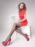 Den härliga kvinnan med långa sexiga ben klädde elegant posera i studion - full kropp Arkivfoton