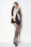 Den härliga kvinnan med långa sexiga ben klädde elegant posera i th fotografering för bildbyråer