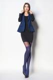 Den härliga kvinnan med långa sexiga ben klädde elegant posera i th Royaltyfria Bilder
