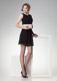 Den härliga kvinnan med långa sexiga ben klädde retro elegant posera i studion Arkivfoto