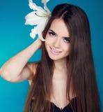 Den härliga kvinnan med långt brunt hår och vit blommar. Attractiv Royaltyfria Foton