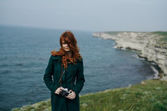 Den härliga kvinnan med långt rött hår rymmer kameran på kanten av berget nära havet royaltyfria foton