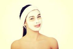 Den härliga kvinnan med leraansiktsbehandling maskerar Royaltyfria Bilder