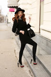 Den härliga kvinnan med mörkt lockigt hår och charmigt leende, bär elegant kläder Arkivbild