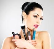 Den härliga kvinnan med makeup borstar Arkivbild