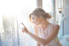 den härliga kvinnan med ny daglig makeup och romantiska krabba frisyren som sitter på fönsterbrädan, drar på exponeringsglas arkivfoton