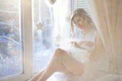 den härliga kvinnan med ny daglig makeup och romantiska krabba frisyren som sitter på fönsterbrädan, drar på exponeringsglas royaltyfri foto