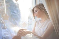 den härliga kvinnan med ny daglig makeup och romantiska krabba frisyren som sitter på fönsterbrädan, drar på exponeringsglas royaltyfria bilder