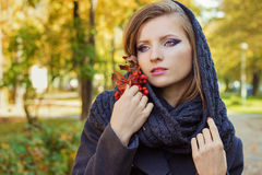 Den härliga kvinnan med rönnen i hand med den härliga makeupen med en halsduk på hennes huvud går i parkera i solig dag för höst Fotografering för Bildbyråer