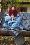 Den härliga kvinnan med rött hår i hösten parkerar att sitta på en bänk med skyler och att täcka hennes framsida med en bok Höstb royaltyfria foton