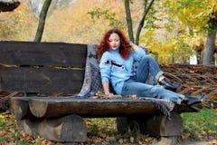 Den härliga kvinnan med rött hår sitter på en bänk och läser en bok som ligger närliggande Hösten parkerar bakgrund Närliggande ä arkivfoton