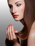 Den härliga kvinnan med rött spikar. Makeup och manikyr.  royaltyfri foto