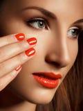 Den härliga kvinnan med rött spikar. Makeup och manikyr. Röda kanter royaltyfria foton