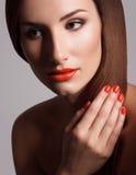 Den härliga kvinnan med rött spikar. Makeup och manikyr. Röda kanter arkivfoto
