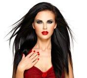 Den härliga kvinnan med rött spikar och kanter Royaltyfri Bild