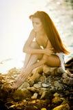 Den härliga kvinnan med skyler i ett baddräktanseende på stranden på solnedgången Stående av en härlig kvinna i bikini på strande Royaltyfri Fotografi