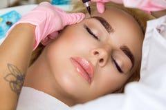 Den härliga kvinnan med slätt, barn flår och att sitta i en kosmetolog En kosmetolog utför att modellera permanenta ögonbryndanan arkivfoton