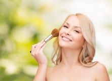 Den härliga kvinnan med stängda ögon och makeup borstar Royaltyfri Bild