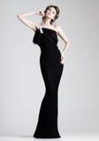 Den härliga kvinnan modellerar att posera i elegant klänning i studion royaltyfri foto